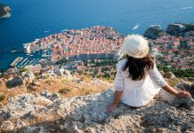 traveller looking at view of dubrovnik old town, in dalmatia, croatia, the prominent travel destination of croatia. dubrovnik old town was listed as unesco world heritage sites in 1979